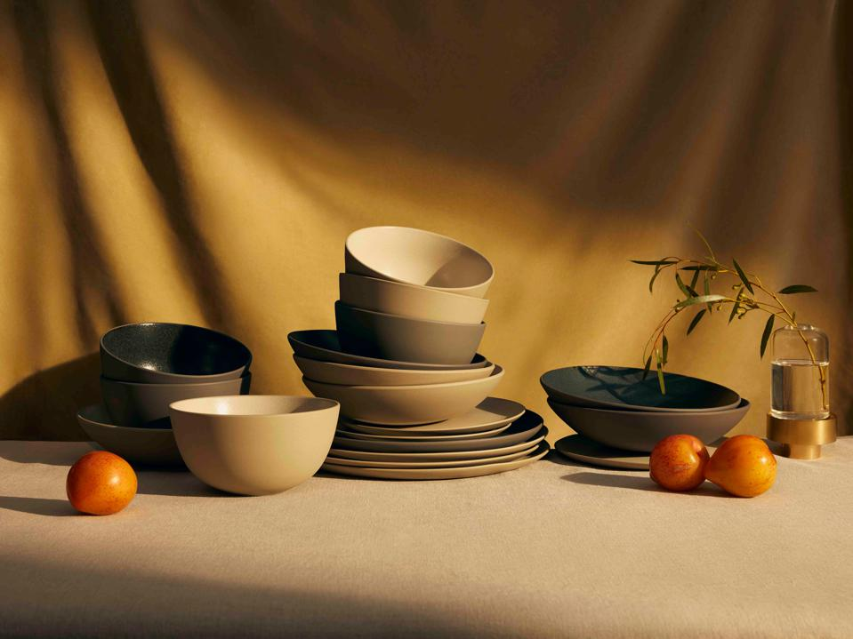 A table holds Material's new tableware, ceramic plates and bowls in cream and stone colors