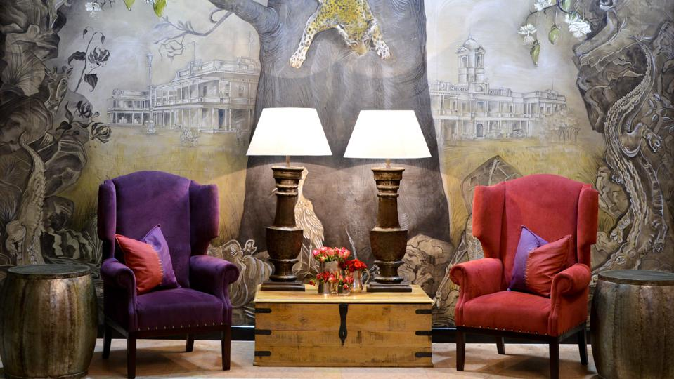 Two chairs sitting in front of a lavish mural featuring a leopard sitting in a tree