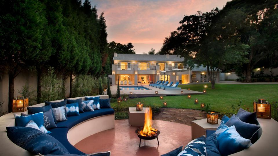 A firepit surrounded by a circular seating area, in the background there's a pool and a large mansion