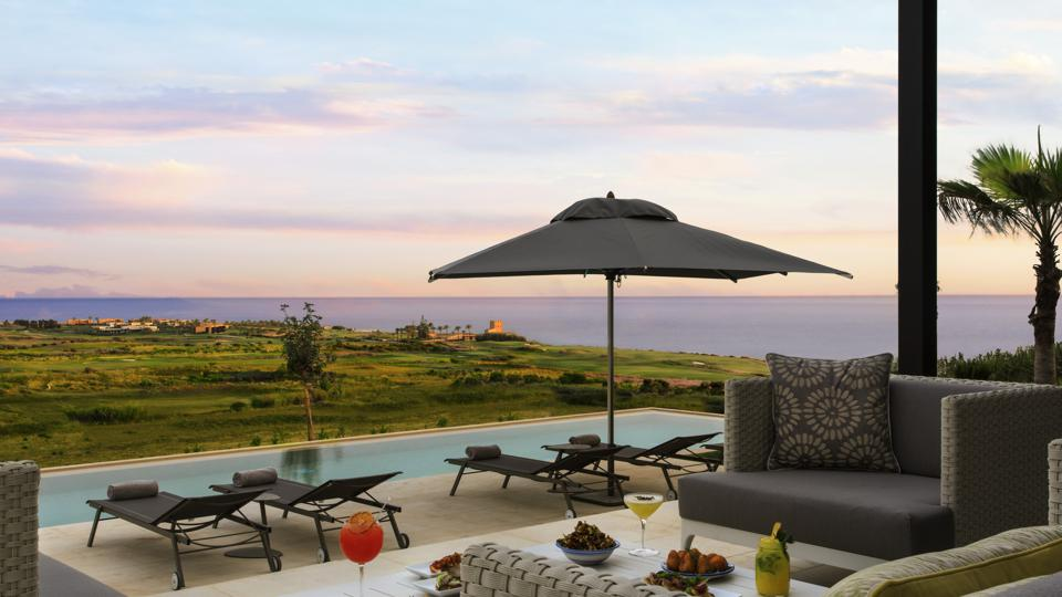 A deck with a pool, a seating area, and an umbrella overlooking a sprawling vineyard