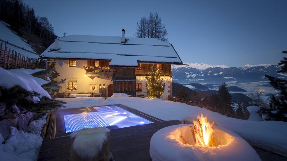 A lodge covered in snow with a fire pit in the foreground and huge mountains in the back