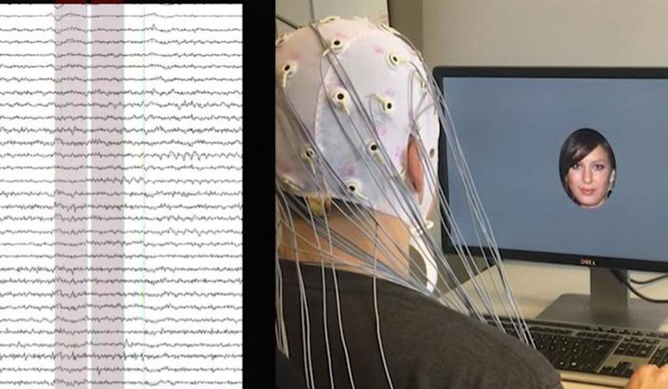 A man wearing EEG leads looks at a digital face.