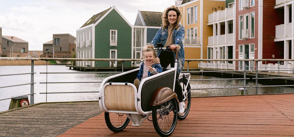 A woman takes her daughter for a ride on a Bunch Bike, the latest winner on Shark Tank.