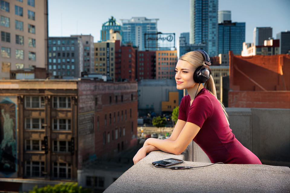 Woman on a city balcony wearing headphones and listening to a smartphone with a THX Onyx.