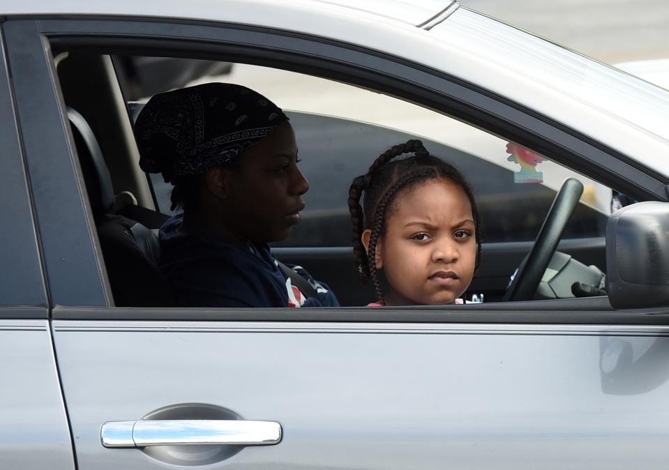 A child and her mother wait in their car at a food...