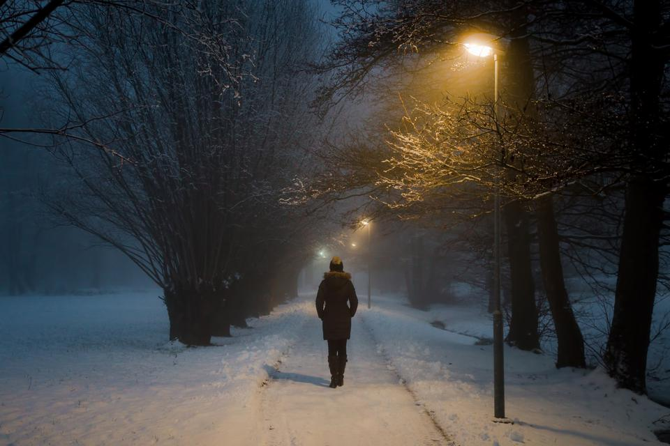 Young woman walking on snowy tree-lined sidewalk under yellow streetlight. Back view.