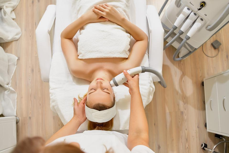 woman close up receiving electric facial massage on microdermabrasion equipment at beauty salon.
