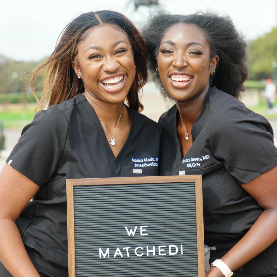Nneka Madu and Jessica Green holding a match sign and smiling in their medical wear.
