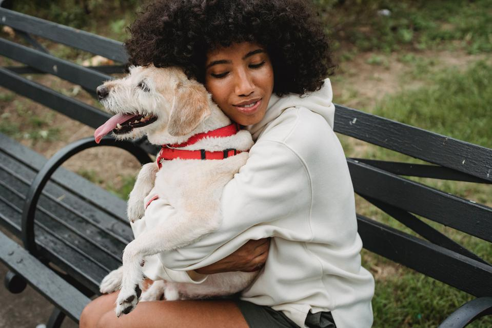 A woman sits on a park bench and hugs her dog