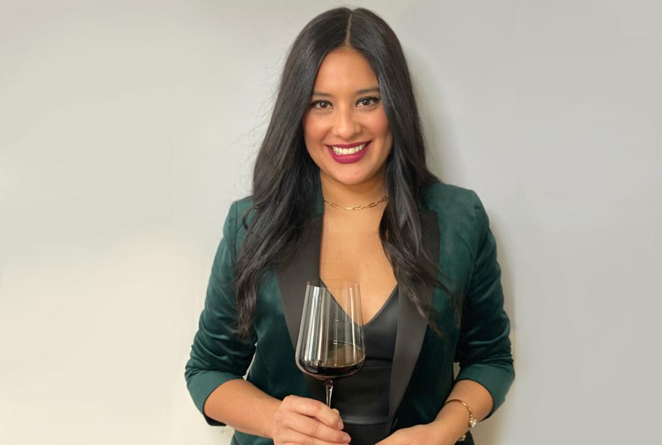 Hispanics in Wine founder Maria Calvert wears a green formal jacket and holds a wine glass