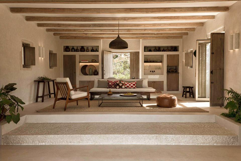 A beige and brown contemporary living room with wood and stone accents and brightly colored burgundy pillows