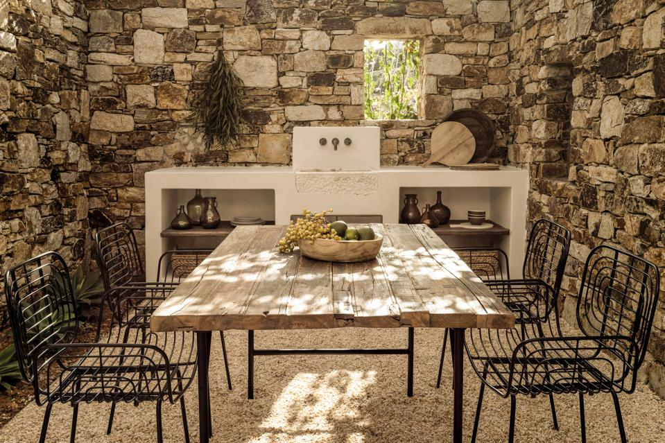 A pebble filled small courtyard surrounded by stone walls with a wood dining table
