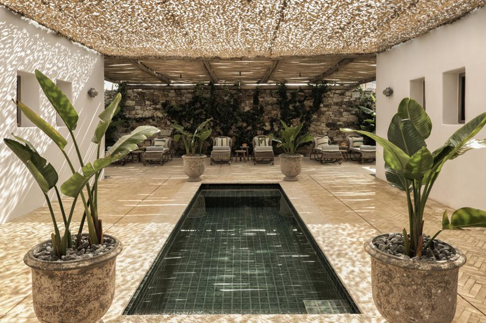 A rectangular pool surrounded by beige stone