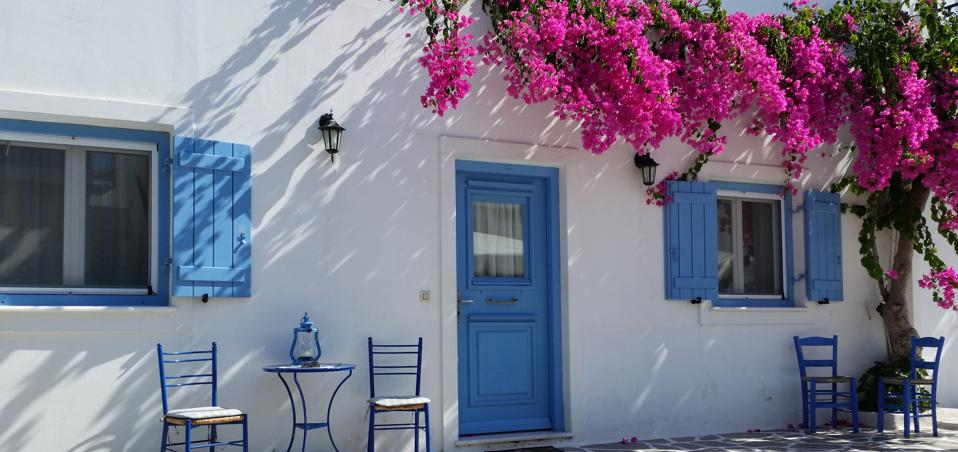 A whitewashed cottage with sea blue shutters and door and a bunch of overhanging magenta flowers
