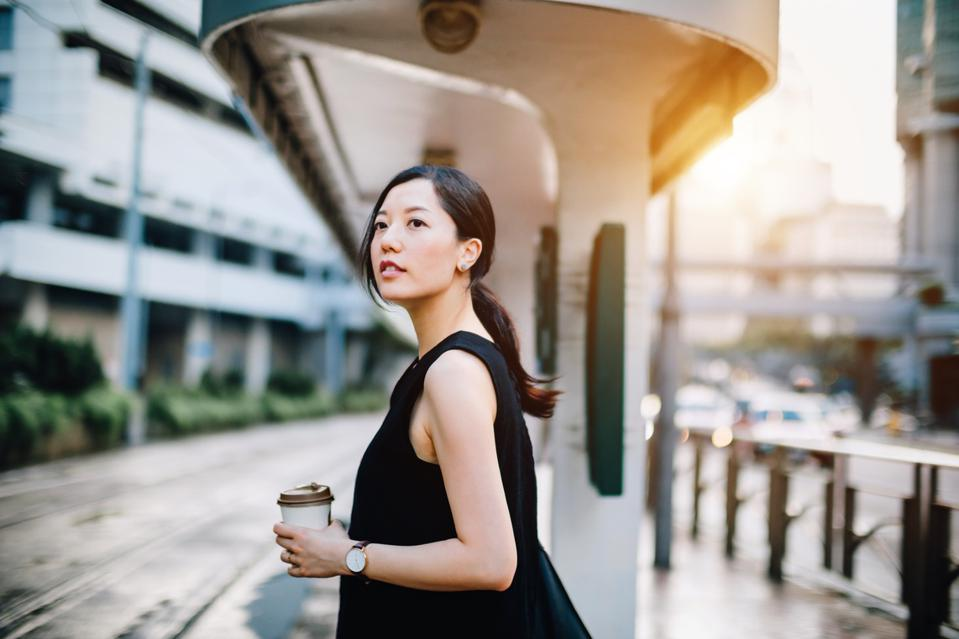 Beautiful young lady holding coffee cup waiting for tram at station in city