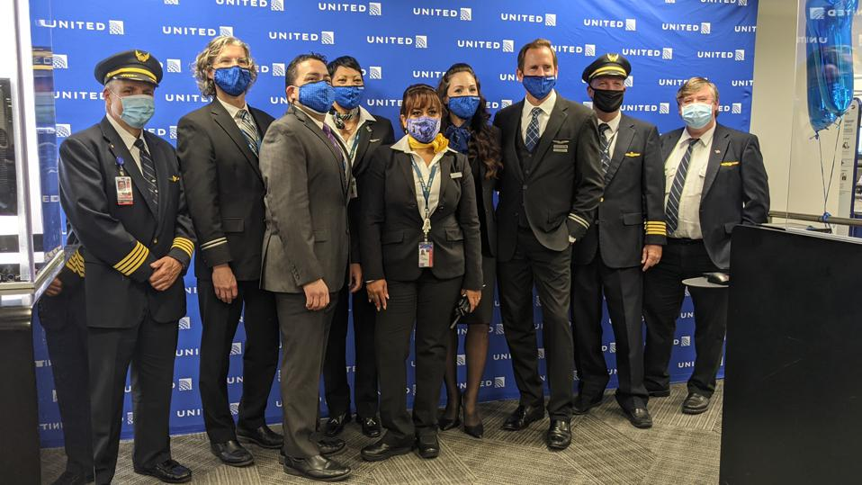 Pilots, cabin crew and gate attendants involved in the United Airlines flight from JFK to San Francisco pose for a photo.