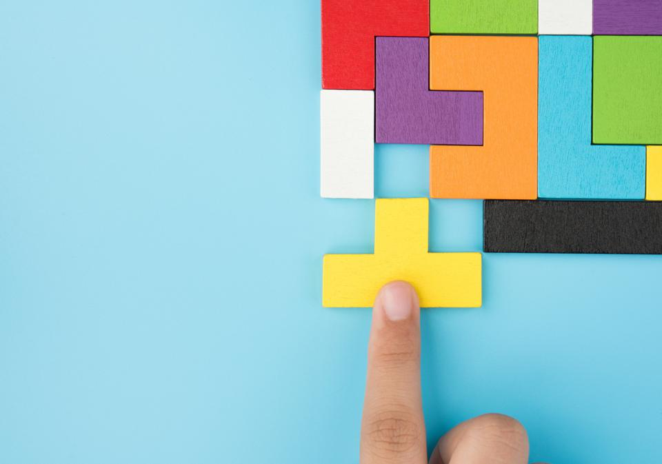 Hand pushing last jigsaw piece to finish puzzle: success planning concept logical thinking