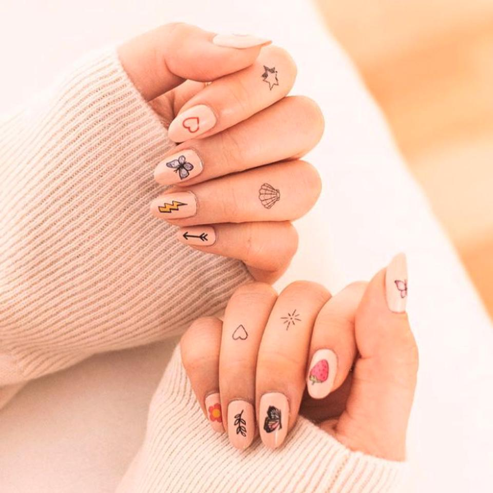 two female hands with nail art on each nail and tattoo on four fingers