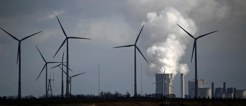Wind turbines turn in front of a coal fired power station belching emissions in Germany.