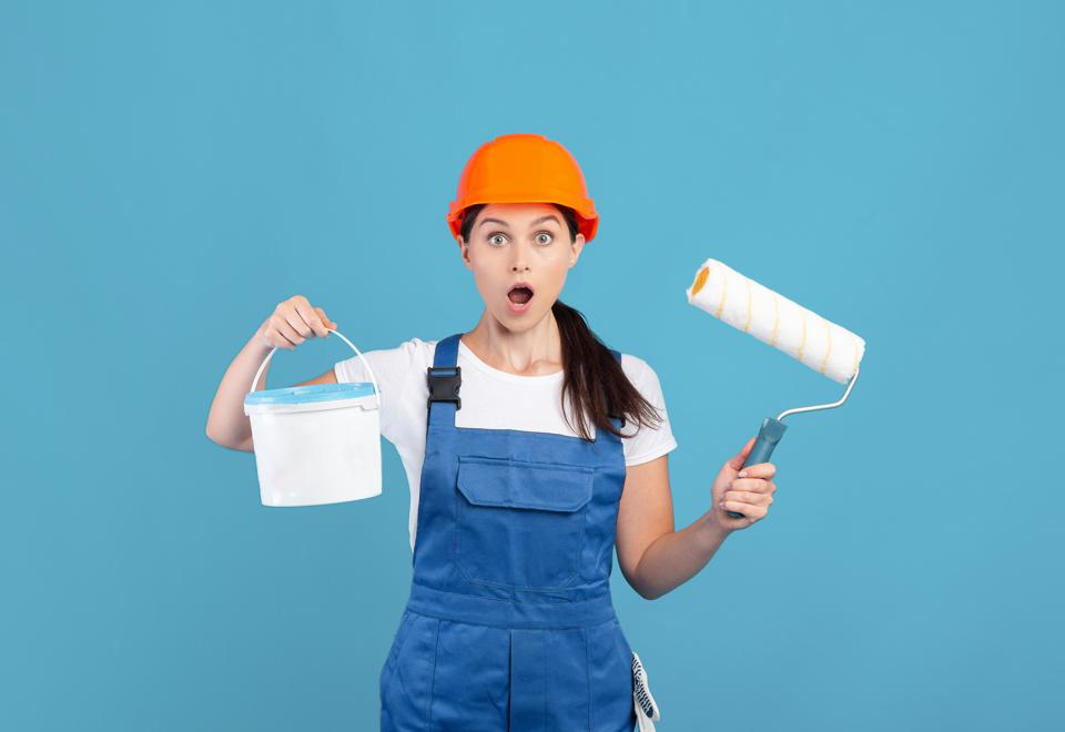 Repair Offer. Shocked Lady In Hard Hat With Paint Roller And Bucket