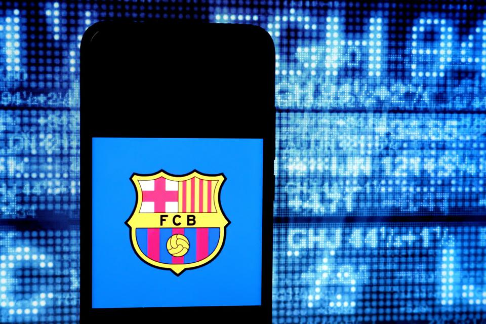 The Barcelona logo seen on a blue phone screen in front of a pixelated background.