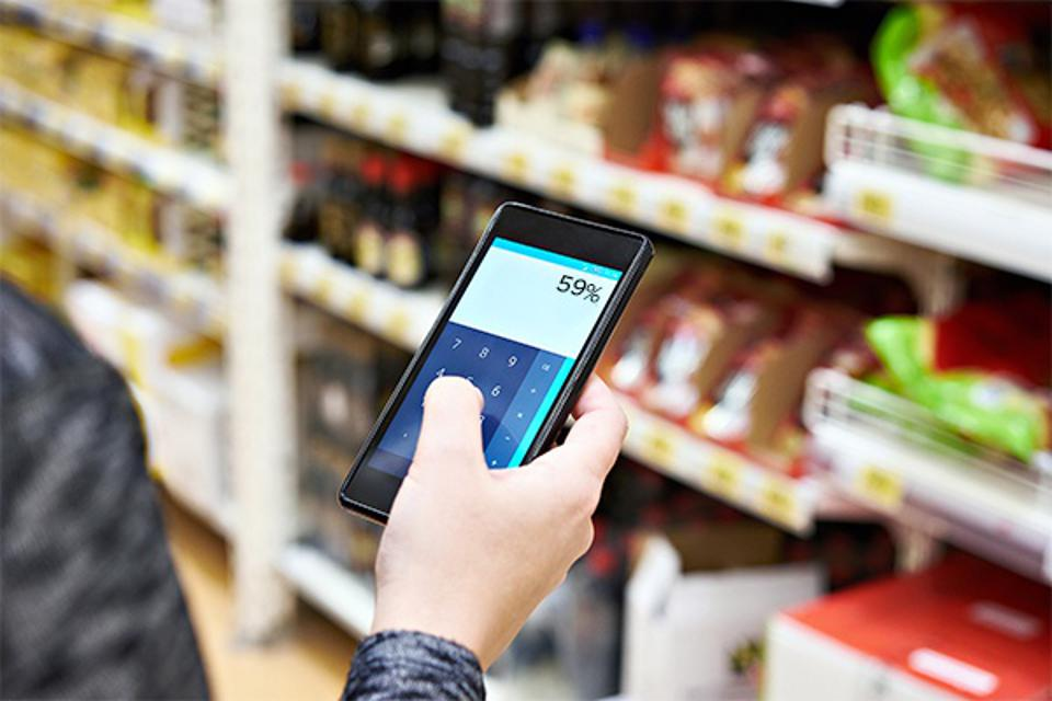 person calculating price of item on phone calculator