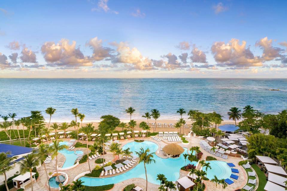 A sprawling pool complex overlooks the beachfront at the Fairmont El San Juan Hotel.