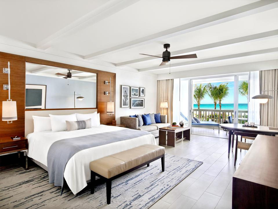 The spacious, modern ocean villa rooms offer dazzling views of the palm-studded beach and crystalline sea.