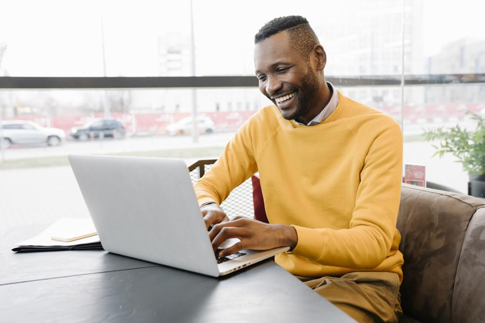 Happy man using laptop in a cafe
