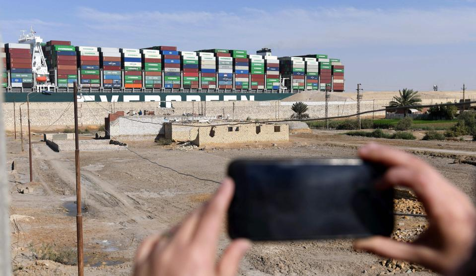 An Egyptian woman takes photos of Evergreen's Ever Given container ship after being fully dislodged from the banks of the Suez Canal on Monday. The vessel, a megaship the length of four football fields, was refloated and the Suez Canal reopened to traffic in the afternoon.