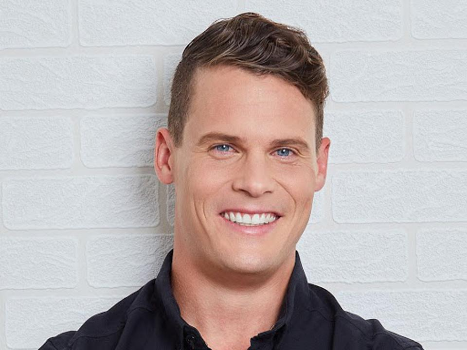 Light brown haired and blue eyed man smiling.