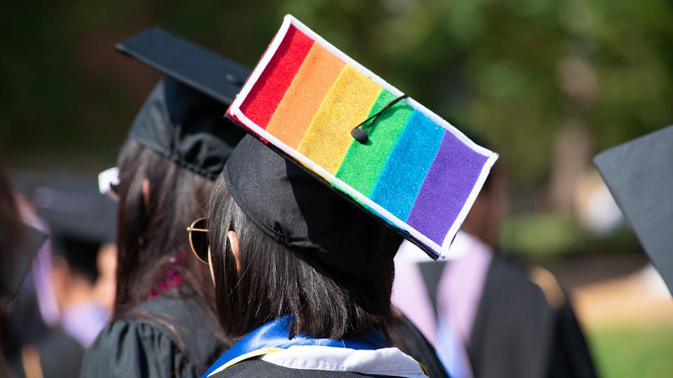 Woman Wears Graduation Cap and Gown Showing Gay Pride