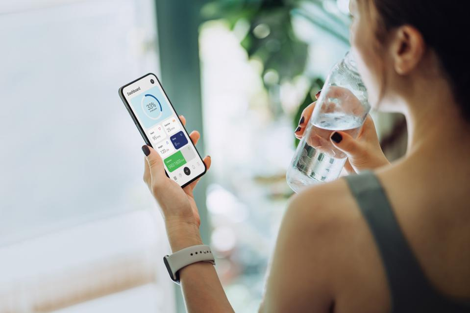 Over the shoulder view of young Asian sports woman refreshing with water and using fitness app on smartphone to monitor her training progress after fitness work out / exercising / practicing yoga at home in the fresh bright morning