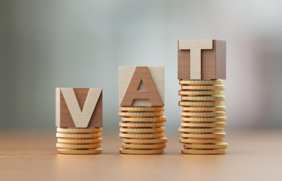 Cube Blocks And Coins Forming VAT Text Over Defocused Background