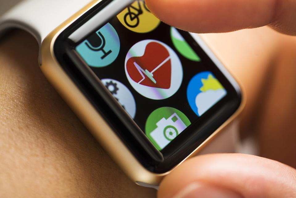 Finger touching heart beat app icon on smart watch screen