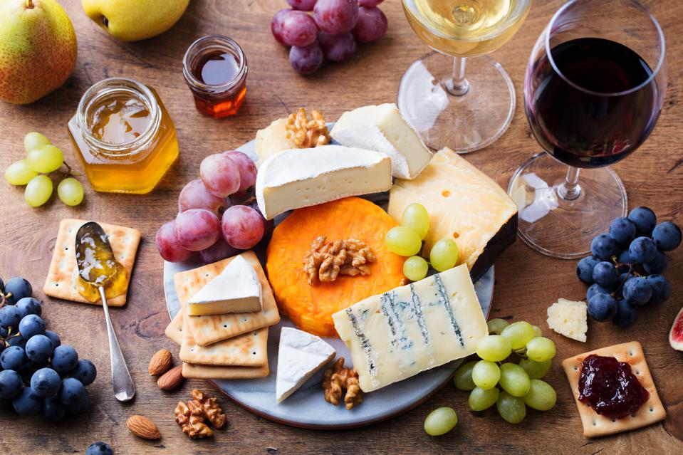 Assortment of French cheese, grapes with red and white wine.