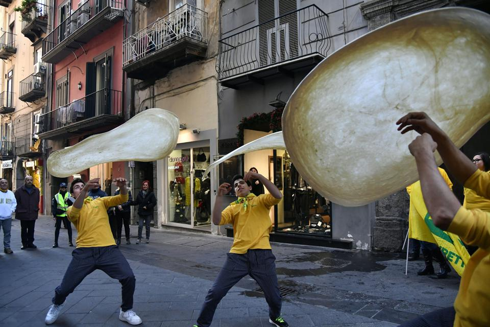 Pizzaioli group in Naples perform ″twirling″ pizza.