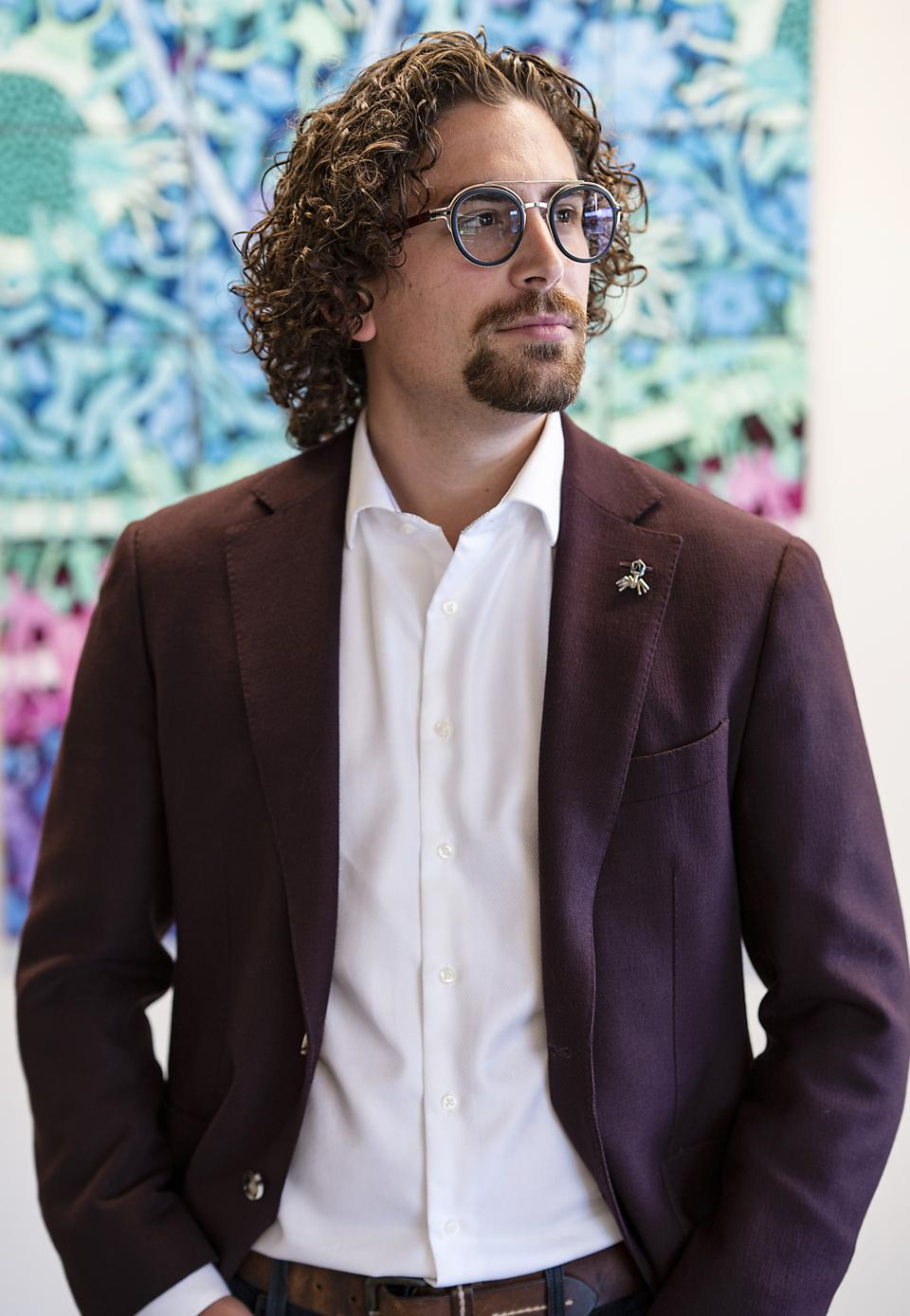 A white man with curly brown hair, glasses and a plum colored suit jacket looking off camera right