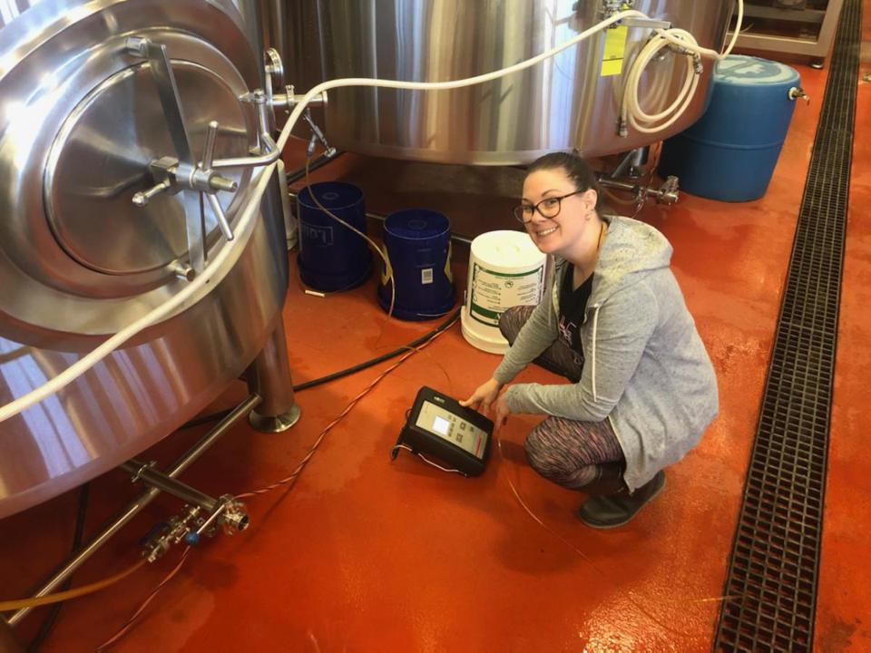 a young woman crouches in front of an electronic device at a brewery