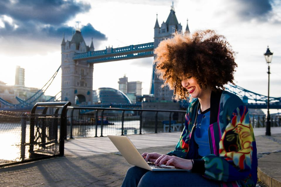 Young girl sitting outdoors, using laptop, Tower Bridge in background, London, England, UK