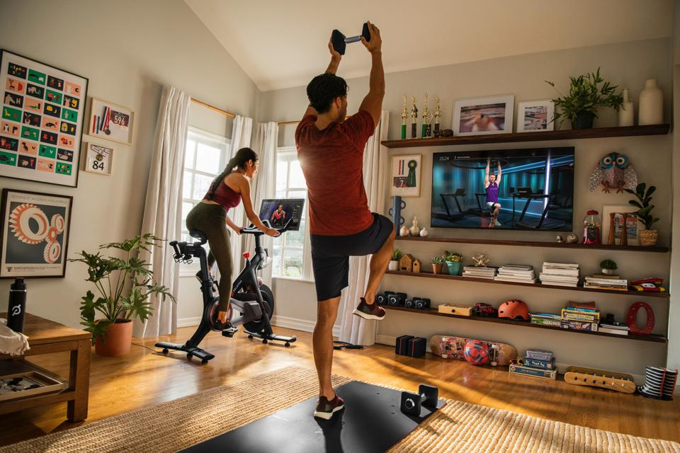 A woman and man workout to Peloton streaming classes at home.