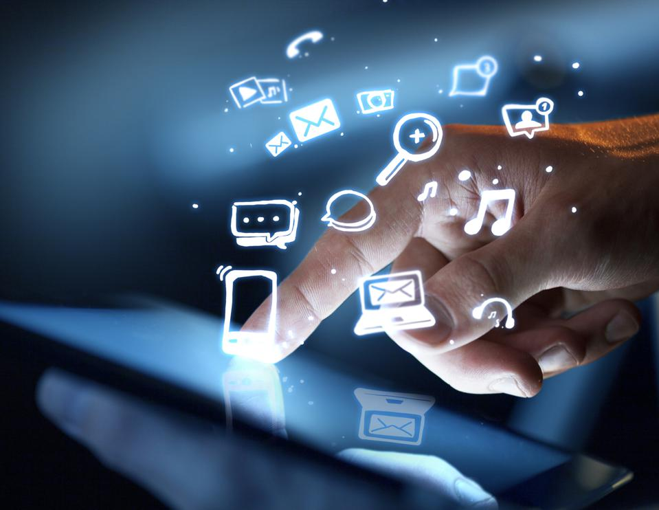 Human hand on a mobile device with app icons floating in the air.