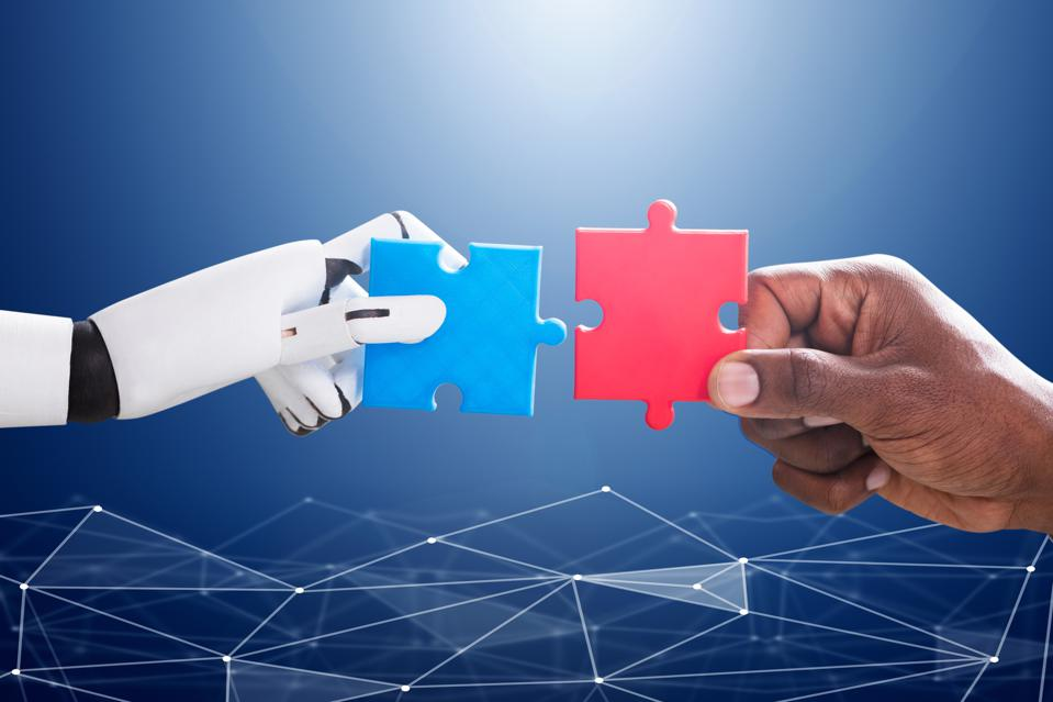 Robot hand holding a puzzle piece. Human hand holding another puzzle piece.