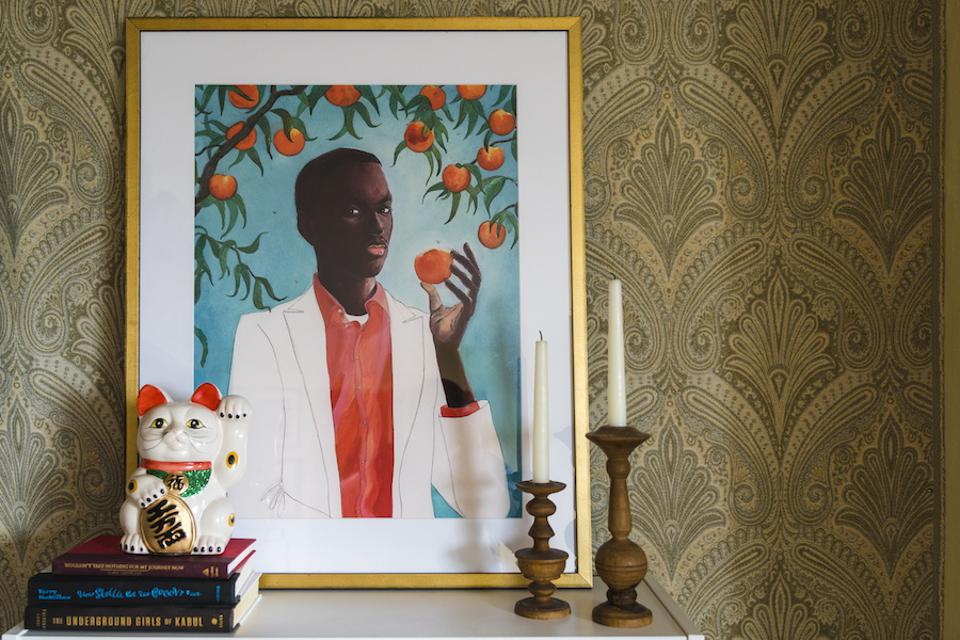 A print of a black man eating an orange on top of a shelf.