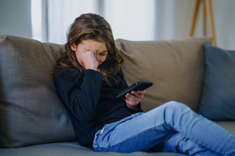 Small girl with smartphone sitting indoors on sofa, crying.