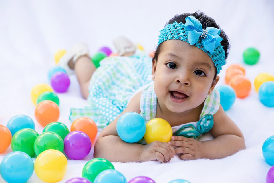 A baby girl lying on her stomach, wearing a headband, surrounded by colorful plastic balls