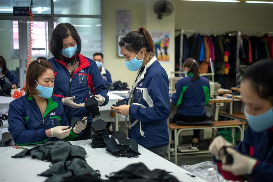 Employees check the quality of protective face masks