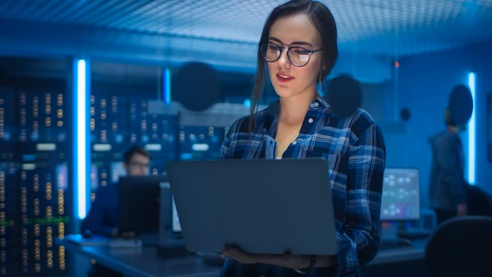 Portrait of a Smart Young Woman Wearing Glasses Holds Laptop. In the Background Technical Department Office with Specialists Working and Functional Data Server Racks