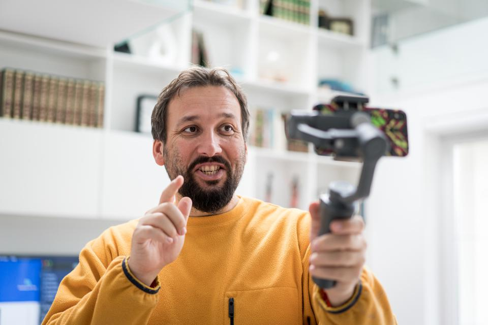 Handsome bearded man making video with smartphone indoors