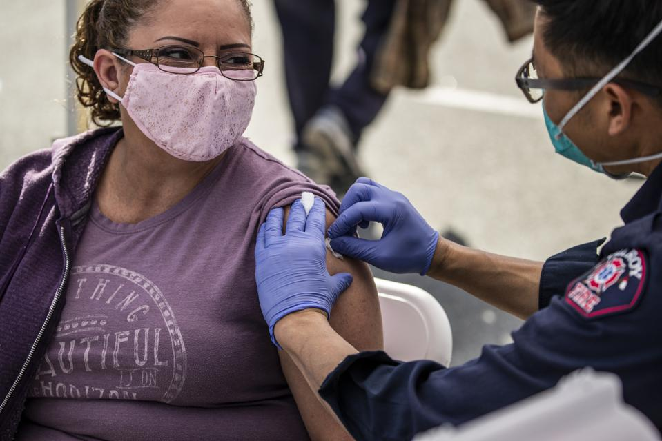 A woman gets her COVID-19 vaccine from a paramedic.